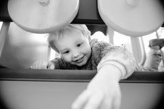 Aktiver netter Kleinkindjunge, der Spaß auf Spielplatz hat Stockbilder