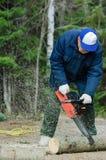Aktiver Senior, der einen gefallenen Baum schneidet Lizenzfreies Stockfoto
