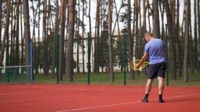 Aktiver sportlicher männlicher Tennisspieler, der einen Ball dient stock footage