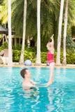 Aktiver Vater, der seine Kleinkindtochter unterrichtet, im Pool auf tropischem Erholungsort zu schwimmen Lizenzfreie Stockfotos