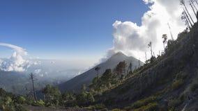 Aktiver Vulkan Fuego umgeben durch Bäume und Wolken, Guatemala stockbild