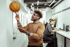 Aktiver zufriedengestellter Kerl mit den Dreadlocks, die Basketballball auf einem Finger rollen stockfotos