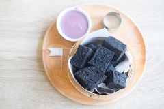 Aktiverat kol ångat bröd och pandan vaniljsås arkivfoto