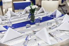 Aktivering för mottagandematställetabell med bordsservis-, servett-, sked-, gaffel- och exponeringsglasgarnering med det blåa fön royaltyfria foton