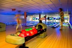 Aktives Bowlingspiel der Leute in der dunklen Bowlingspielhalle Stockbilder