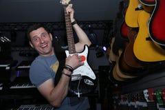Aktives emotionales mit einem L?cheln auf seinem Gesicht ein junger Mann, der eine E-Gitarre vor dem hintergrund der Gitarren in  stockfotografie