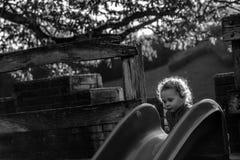Aktives Kind, das auf Freienspielplatz in der Natur spielt Stockbilder