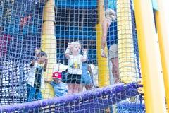 Aktives kleines Kind, das auf kletterndem Netz spielt stockfotografie