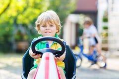 Aktives kleines Kind, das Tretauto im Sommergarten fährt Stockfotos