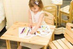 Aktives kleines Vorschulalterskind, nettes Kleinkindmädchen mit dem blonden gelockten Haar, zeichnendes Bild auf Papier unter Ver Stockfotos