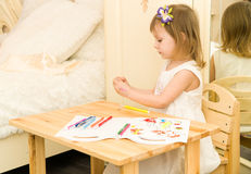 Aktives kleines Vorschulalterskind, nettes Kleinkindmädchen mit dem blonden gelockten Haar, zeichnendes Bild auf Papier unter Ver Stockfotografie