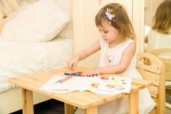 Aktives kleines Vorschulalterskind, nettes Kleinkindmädchen mit dem blonden gelockten Haar, zeichnendes Bild auf Papier unter Ver lizenzfreies stockbild