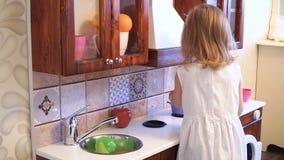 Aktives kleines Vorschulalterskind, nettes Kleinkindmädchen mit dem blonden gelockten Haar, zeigt das Spielen der Küche, gemacht  stock video footage