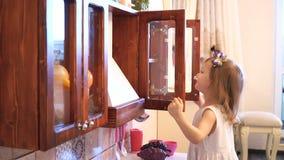 Aktives kleines Vorschulalterskind, nettes Kleinkindmädchen mit dem blonden gelockten Haar, zeigt das Spielen der Küche, gemacht  stock video