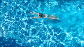 Aktives Mädchen Swimmingpoolin der luftbrummenansicht vom Schwimmen der oben genannten, jungen Frau im blauen Wasser, tropische F stockbilder