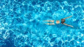 Aktives Mädchen Swimmingpoolin der luftbrummenansicht vom Schwimmen der oben genannten, jungen Frau im blauen Wasser, tropische F stockfotos