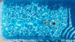 Aktives Mädchen Swimmingpoolin der luftbrummenansicht vom Schwimmen der oben genannten, jungen Frau im blauen Wasser, tropische F lizenzfreie stockfotos