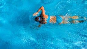 Aktives Mädchen Swimmingpoolin der luftbrummenansicht vom Schwimmen der oben genannten, jungen Frau im blauen Wasser, tropische F lizenzfreies stockfoto