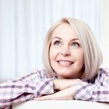 Aktives schönes Frauenoben lächeln von mittlerem Alter freundlich und zu Hause schauen im Wohnzimmer Gesichtsabschluß der Frau ob stockfotos