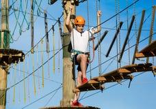 Aktives sportliches Kind im Sturzhelm, der Tätigkeit im Erlebnispark mit aller kletternden Ausrüstung tut Aktive Kinder lizenzfreie stockfotos