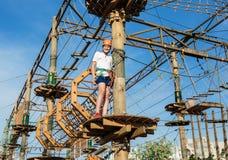 Aktives sportliches Kind im Sturzhelm, der Tätigkeit im Erlebnispark mit aller kletternden Ausrüstung tut stockfotos