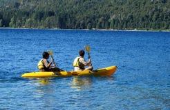 Aktivt folk i kajaker som bär lifejackets med skovlar Fotografering för Bildbyråer