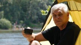 Aktivt gamlingbegrepp Hög manlig fotvandrare som sitter i tältet och att dricka te eller kaffe Gullig man med grått hår close upp arkivfilmer