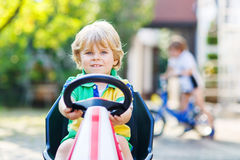Aktivt litet barn som kör den pedal- bilen i sommarträdgård Arkivfoton
