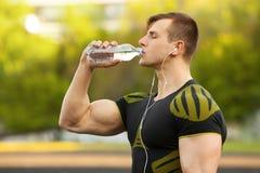 Aktivt mandricksvatten från en flaska som är utomhus- Den muskulösa mannen släcker törstat Arkivbilder