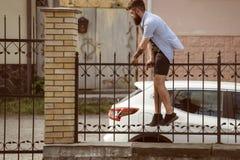 Aktivt och driftigt Hipsterklättrare Hipster som får över staketet Skäggig man som klättrar i moderiktig hipsterstildräkt arkivbilder