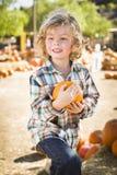 Aktywna chłopiec Trzyma Jego bani przy Dyniową łatą Obrazy Royalty Free