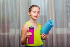 Aktywna dziecka mienia ćwiczenia mata i bidon w domu Obrazy Stock