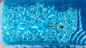 Aktywna dziewczyna w basenu trutnia powietrznym widoku z góry, młoda kobieta pływa w błękitne wody, tropikalny wakacje, wakacje n zdjęcia royalty free