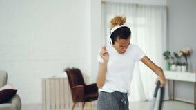 Aktywna dziewczyny gospodyni domowa sprząta mieszkanie używać próżniowego cleaner i słuchanie muzyka z hełmofonami, taniec i zbiory