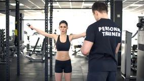 Aktywna kobieta robi ćwiczeniu z dumbbells podczas treningu z osobistym trenerem fotografia royalty free