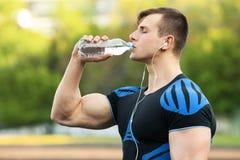 Aktywna mężczyzna woda pitna od butelki, outdoors Potomstwa dostosowywali samiec quenches pragnienie Obrazy Royalty Free
