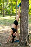 Aktywna młoda brunetki kobieta robi sił ćwiczeniom z nogami w górę przewodzi puszek blisko drzewa w parku, w lato czasie obrazy royalty free
