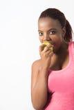 Aktywna młoda kobieta je jej zielonego jabłka Fotografia Stock