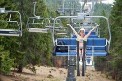 Aktywna naga narciarka ma zabawę na narciarskim dźwignięciu i jazdie do wierzchołka góra z narciarskim wyposażeniem Fotografia Royalty Free