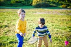 Aktywna preschool dziewczyna, chłopiec bawić się badminton w plenerowym sądzie w lecie i Dzieciak sztuki tenis Szkoła bawi się dl fotografia stock
