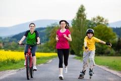 Aktywna rodzina - matka i dzieciaki biega, jechać na rowerze, rollerblading Fotografia Stock