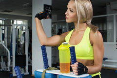 Aktywna seksowna kobieta w sportswear obsiadaniu na sporta wyposażeniu pokazuje dętych bicepsy Bawi się odżywianie Amino kwasy Fotografia Stock
