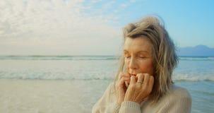 Aktywna starsza Kaukaska kobiety pozycja z oczami zamykał na plaży 4k zbiory wideo