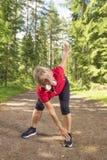Aktywna starsza kobieta rozgrzewkowa up przed ćwiczeniem zdjęcie stock