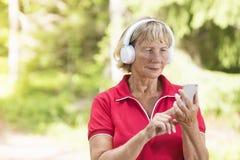 Aktywna starsza kobieta używa sport tropi app zdjęcie royalty free