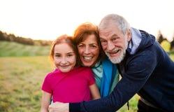 Aktywna starsza para z wnuczki pozycją w naturze przy zmierzchem zdjęcia royalty free