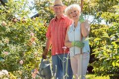Aktywna szczęśliwa starsza kobiety pozycja obok jej męża podczas ogrodowej pracy obraz stock