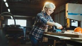 Aktywna w średnim wieku kobieta wybiera drewno w warsztacie Pojęcie profesjonalnie ukierunkowywająca niepłonna nowożytna kobieta  zdjęcie stock