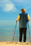Aktywnej kobiety starszy północny odprowadzenie na plaży Od behind Zdjęcia Stock