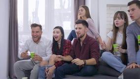 Aktywni fan piłki nożnej przyjaciół faceci z dziewczynami ogląda sport rywalizację na telewizji i radośnie wita cel zbiory